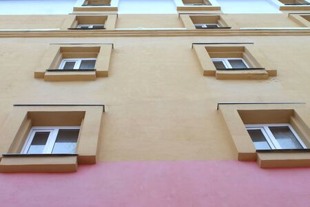Plastic windows in a modern brick high-rise house with plastered surface. Bottom view. Stock photo modern urban development for web and print.