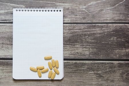 Notepad with a blank white sheet in a checker paper with pills lies on the background of wooden boards.