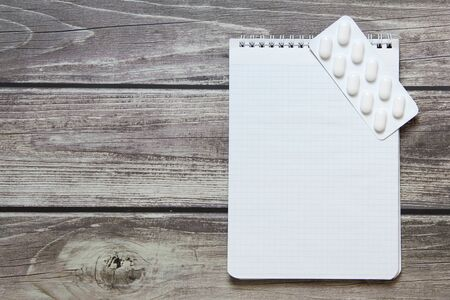 Notepad with a blank white sheet in a checker paper with pills in a blister lies on the background of wooden boards. Stock Photo