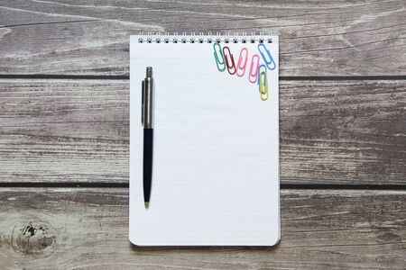 Notepad with a blank white sheet in a checker paper and with ball pen and with paper clips lies on the background of wooden boards.