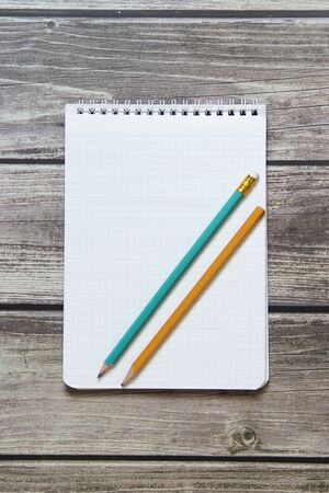 Notepad with a blank white sheet in a checker paper with two simple graphite pencil lies on the background of wooden boards Stock Photo