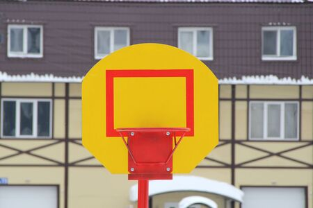 Bright yellow stand with a red ring for a basketball sword against a wall of a residential building, outdoor sports ground. Stock horizontal format photo with empty space for text and design. Banque d'images - 140990114