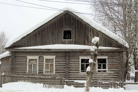 Old wooden one-story house on a background of a winter landscap. Outdated russian urban architecture. Stock photo for web and print with empty space for text. Banque d'images - 140990202