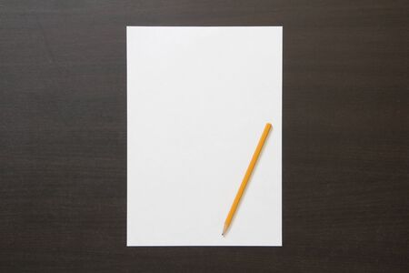 Template of white paper and pencil on dark wenge color wooden background. Concept of new idea, business plan and strategy, development of content.Stock photo with empty space for text and design.