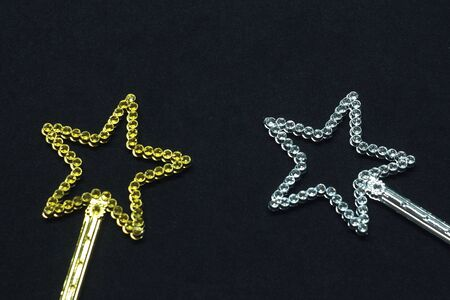Two magic wands golden and silver color with a star on top with rhinestones. Plastic children toy on black background. Stock photo for web print, background and wallpaper.