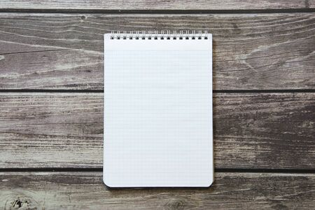 Notepad with a blank white sheet in a checker paper lies on the background of wooden boards Standard-Bild
