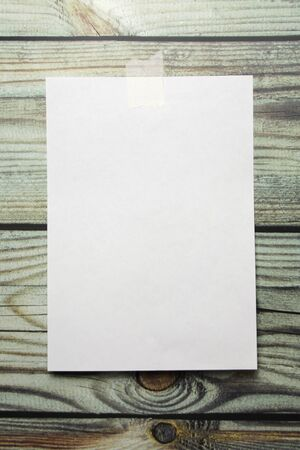 A white sheet of A4 paper hanging on a wall glued with a piece of paper tape on a wooden background.