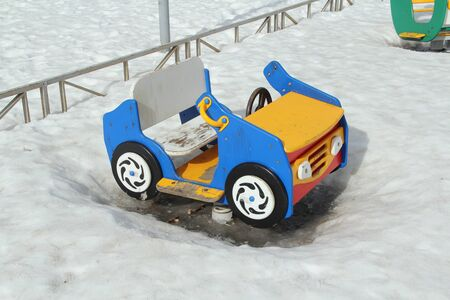 Childrens swing in the form of a car on the playground against the background of winter snowdrifts. Concept of childrens entertainment and street games. Stock photo for web and print with empty space for text.