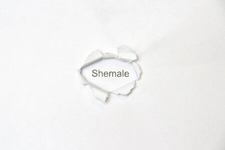 Word shemale on white isolated background, the inscription through the wound hole in paper. Concept of gender identity and sexual minorities. Stock photo for web and print with empty space for text