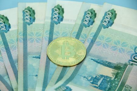 Russian money paper bills of one thousand rubles denominated in a fan. Bitcoin is on top.