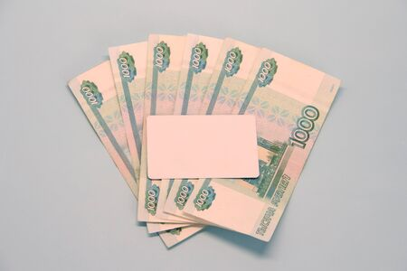 Russian money paper bills of one thousand rubles denominated in a fan. A white empty plastic card lies on top. Place for text and layout for design.