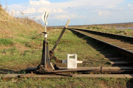 Railway arrow in black with a lever and pointer in Russia. The device for the transfer of rails at intersections for trains. Technical element of the railway industry.