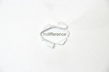 Word indifference on white isolated background, the inscription through the wound hole in the paper. Stock photo for web and print with empty space for text and design. 版權商用圖片
