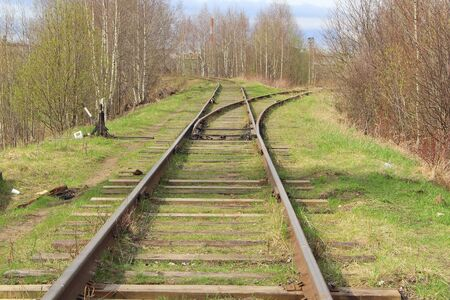 The railway stretching into the distance against the background of young green grass and trees in spring.