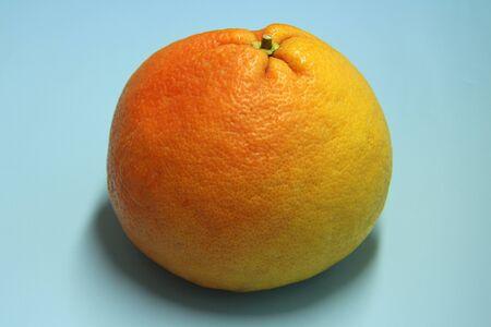 Red-orange whole uncut grapefruit on a blue background. Juicy citrus fruit.