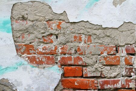 Old cracked brick wall with cracks and hollows. Grunge stylish background with grungy texture. Stock photo for web and print with empty space for text and design 写真素材