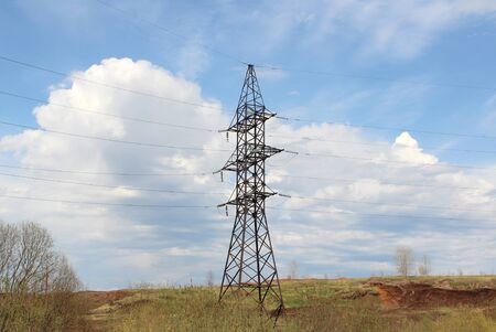 Iron pylon of a high voltage power line stands in a field against a blue sky.