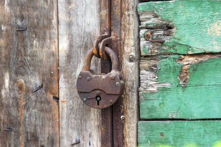 A old iron padlock hangs on the wood door. Locked door to the premise. Concept of protection, incarceration, protection, prison.