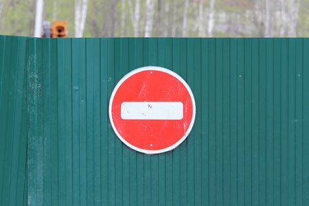Red round road sign with white stripe prohibiting movement on the green fence of sheet iron. Do not enter. concept of prohibition, dead end, hopelessness and stop. Reklamní fotografie