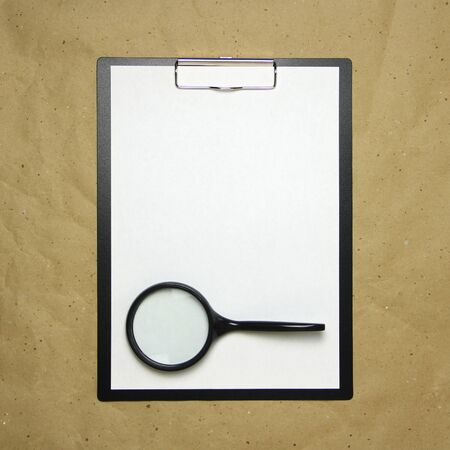 A tablet with a white sheet of A4 format with magnifier on a beige craft paper. Concept of analysis, study, attentive work. Stock photo with empty place for your text and design.