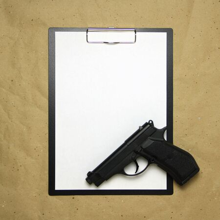 A tablet with a white sheet of A4 format with gun on a beige craft paper. Concept of the legal system, criminal organizations, security services. Stock photo with empty place for your text and design. Stok Fotoğraf