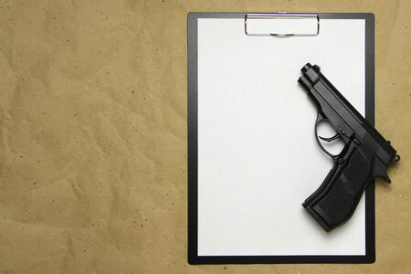 A tablet with a white sheet of A4 format with gun on a beige craft paper. Concept of the legal system, criminal organizations, security services. Stock photo with empty place for your text and design. Banque d'images