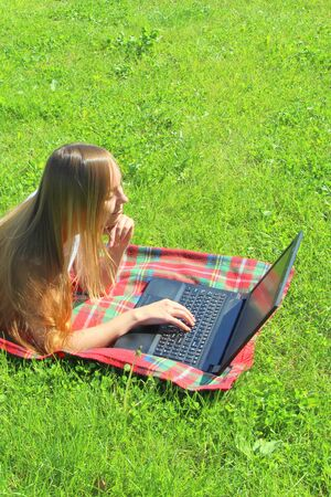 A beautiful young white girl in a white T-shirt and with long hair lies on a red plaid, on green grass, on the lawn and working behind a black laptop.