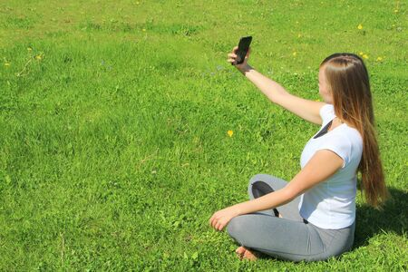 A beautiful young white girl in a white t-shirt and with long hair sitting on green grass, on the lawn and takes a selfie.