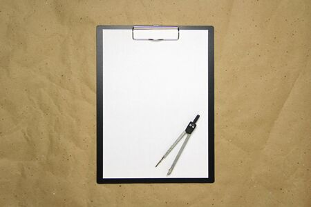 A tablet with a white sheet of A4 format with divivder on a beige craft paper. Concept of accurate measurements, study and construction. Stock photo with empty place for your text and design.