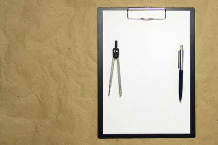 A tablet with a white sheet of A4 format on a beige craft paper with pen and divider. Concept of accurate measurements, study and construction. Stock photo with empty place for your text and design.