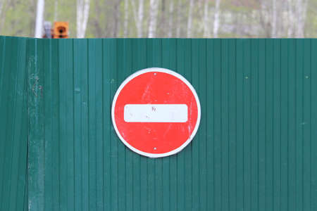 Red round road sign with white stripe prohibiting movement on the green fence of sheet iron. Do not enter. concept of prohibition, dead end, hopelessness and stop.