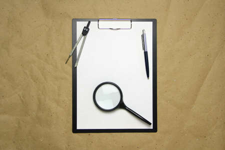 A tablet with a white sheet of A4 format with magnifier, pen and divider on a beige craft paper. Concept of analysis, study, attentive work. Stock photo with empty place for your text and design.