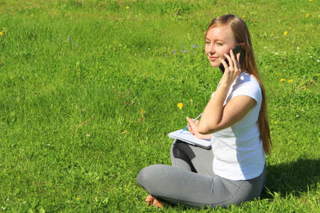 A beautiful young white girl in a white t-shirt and with long hair sitting on green grass, on the lawn and working behind a black laptop and talking on a cell phone and writes with a pen in a notebook.