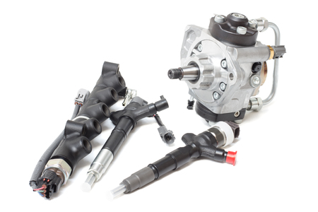 solenoid injectors for diesel fuel lying on a white background with a rod and a fuel injection pump