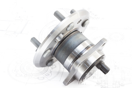 metal parts: hub with bearing and ABS sensor on the background of drawings and plans Stock Photo