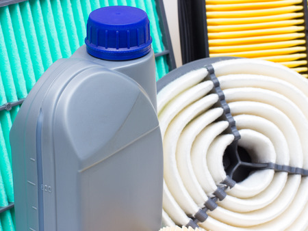 lubricate: Group of various automotive filters and a liter bottle of motor oil or brake fluid. The horizontal arrangement of the picture Stock Photo