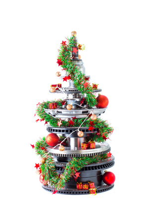 Abstract christmas tree of car parts on a white background. Decorated with Christmas toys, garland Standard-Bild