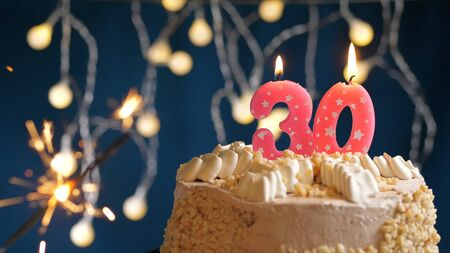Birthday cake with 30 number pink candles and burning sparkler on blue backgraund. Close-up view Stock Photo