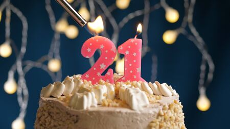 Birthday cake with 21 number candle on blue backgraund set on fire by lighter. Close-up view candles Banque d'images
