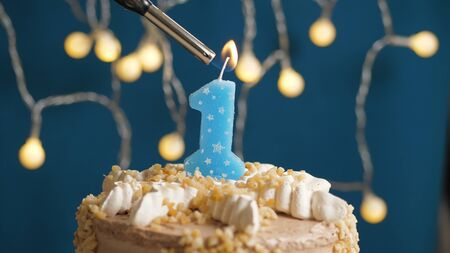 Birthday cake with 1 number candle on blue backgraund set on fire by lighter. Close-up view