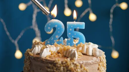 Birthday cake with 25 number candle on blue backgraund set on fire by lighter. Close-up view
