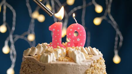 Birthday cake with 19 number candle on blue backgraund set on fire by lighter. Close-up view candles