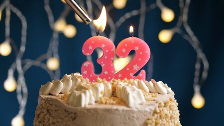 Birthday cake with 32 number candle on blue backgraund set on fire by lighter. Close-up view candles