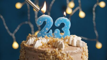 Birthday cake with 23 number candle on blue backgraund set on fire by lighter. Close-up view Banque d'images