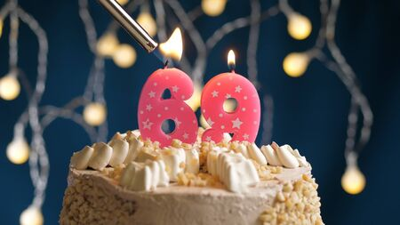 Birthday cake with 69 number candle on blue backgraund set on fire by lighter. Close-up view candles