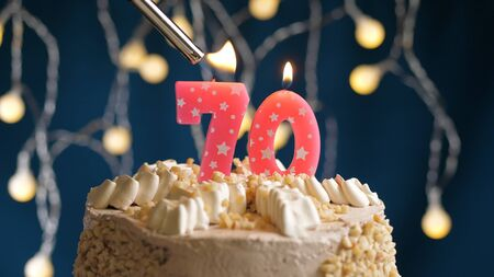 Birthday cake with 70 number candle on blue backgraund set on fire by lighter. Close-up view candles