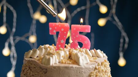 Birthday cake with 75 number candle on blue backgraund set on fire by lighter. Close-up view candles