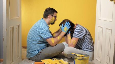 Guy and girl are sitting at wall just painted, woman is crying with joy, man is sorry for her. Apartment renovation, wall painting, work completed concept. Medium shot