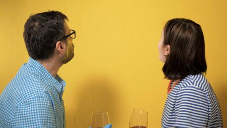 Guy and girl are sitting by freshly painted wall and drinking wine and looking at wall . They are tired, but happy with themselves. Apartment renovation, wall painting, work completed concept Imagens