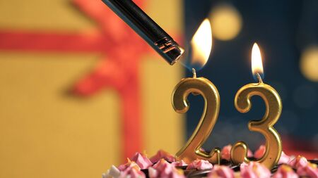 Birthday cake number 23 golden candles burning by lighter, background gift yellow box tied up with red ribbon. Close-up view Archivio Fotografico